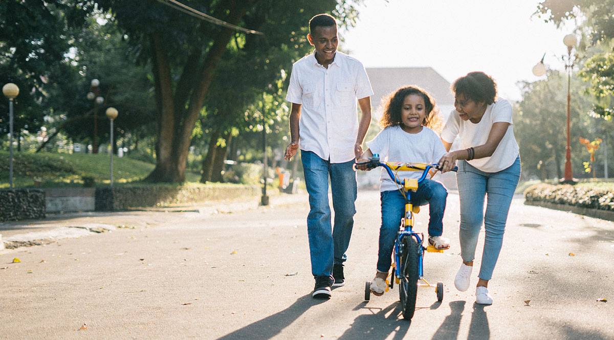 parents teaching daughter to ride bike with training wheels